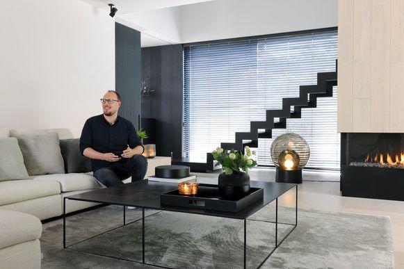 Bart Appeltans in de woonkamer met op de achtergrond de zwarte stalen trap van Genico.