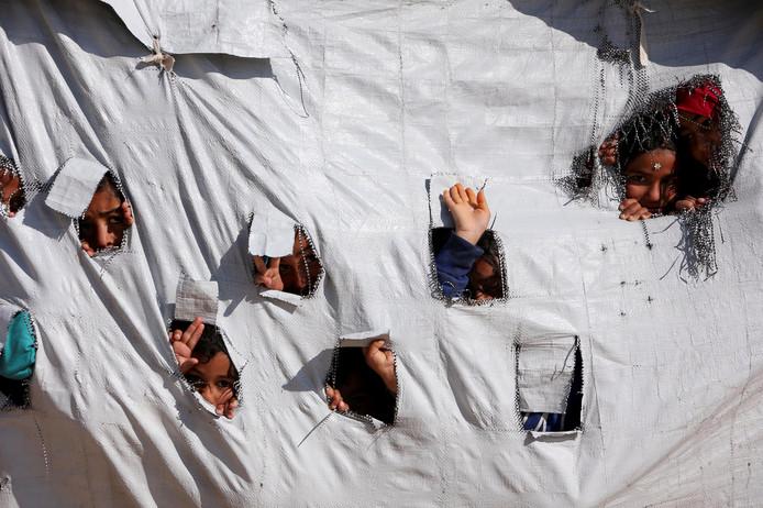 Kinderen kijken door gaten in een tentdoek in Al-Hol, waar ook Nederlandse vrouwen verblijven.