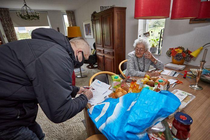 Vrijwilliger Chris Maltby helpt mevrouw Vroon-van Blijkshof met haar boodschappen.