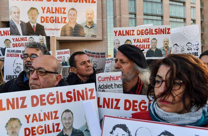 Demonstranten bij een rechtbank in Istanboel met foto's van de gevangengenomen Turkse journalisten.