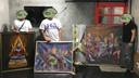 Kunsthandelaar Pakorn Porncheewarakun onherkenbaar tussen de schilderijen die samen met anderen van de kunstenares kocht