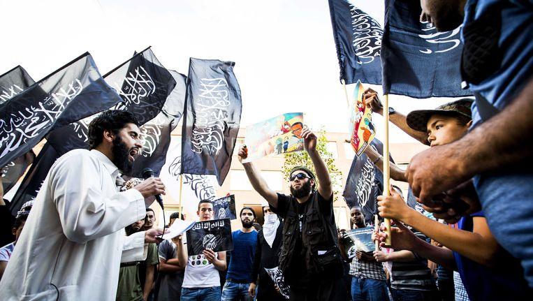 Demonstranten zwaaien met (onder andere) IS-vlaggen tijdens een betoging in de Haagse Schilderswijk. Het OM heeft de afgelopen weken ronselaars en jihadisten opgepakt in onder meer Den Haag en Huizen. Beeld ANP