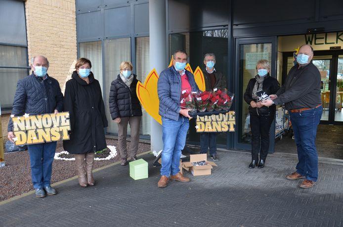 De organisatoren van 'Ninove Danst' schenken kerstrozen aan wzc Klateringen.