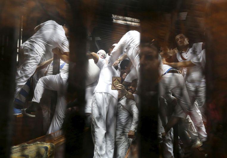 Een wirwar van gedaagden bidt met de Koran in de hand in de rechtbank in Cairo.  Beeld REUTERS