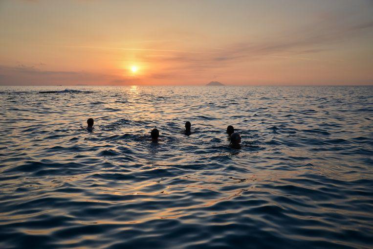Zwemmen bij zonsondergang in de Tyrreense Zee, aan de horizon een (rokende) vulkaan  Stromboli. Beeld Theo Stielstra