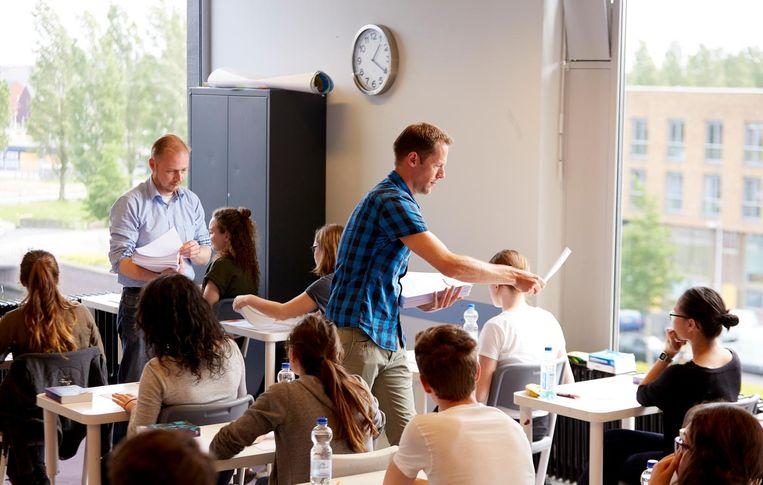 Docenten delen examens uit op een middelbare school. Beeld anp