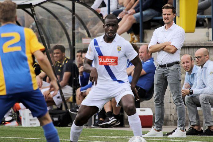 Niels van Casteren (rechts, staand) ziet toe hoe zijn ploeg speelt tegen Jong Vitesse.