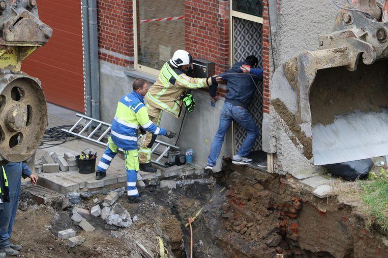 Een bewoner wordt door enkele helpende handen in zijn woning geholpen.