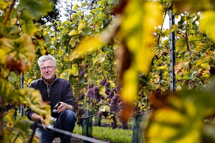 Henk Aarts met een fles wijn van Wijngoed Zurrick.