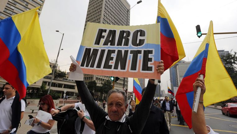 Een man in Colombia houdt een bord vast met Farc liegt.