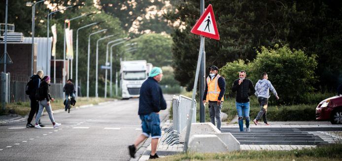 Arbeidsmigranten arriveren bij slachthuis en vleesverwerker Van Rooi Meat in Helmond. Deze slachterij moest dicht vanwege een te hoog aantal coronabesmettingen.