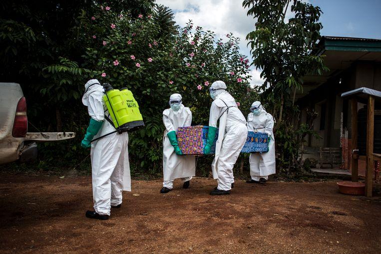 Hulpverleners tillen het lichaam van een patient, vermoedelijk besmet met het ebola-virus,  in de laadbak van een auto in het dorp Mangina in Congo. Beeld AFP