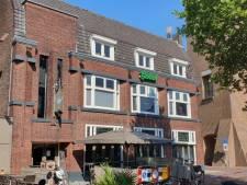 Man met ontbloot bovenlijf klimt op dak van café in Hengelo en gooit spullen op agenten