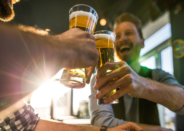 Close up of happy men having fun while toasting with beer in a bar.