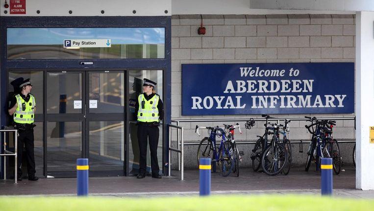 Agenten bewaken de ingang van het ziekenhuis waar prins Philip opgenomen werd. Beeld epa