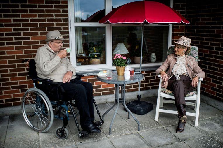 Birthe Nielsen bezoekt haar man Niels in het verzorgingshuis. Dat gebeurt buiten en met twee meter afstand. Beeld EPA