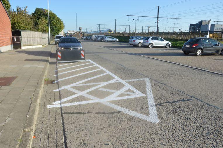 Een nieuwe wegmarkering werd aangebracht over een oude markering in de Spoorweglaan, wat een vreemd beeld oplevert.