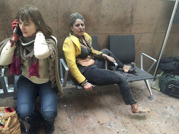 Twee gewonde vrouwen vlak na de aanslag op het Belgische vliegveld. Beeld reuters