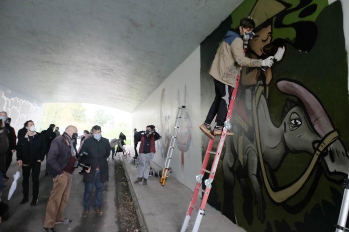 Een graffitikunstenaar aan het werk in de blauwe brug.