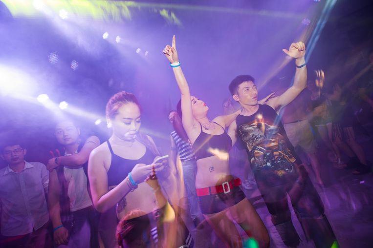 Jongeren dansen op elektronische muziek in een voormalige fabriek in Jinghua in het oosten van China. Beeld Corbis via Getty Images