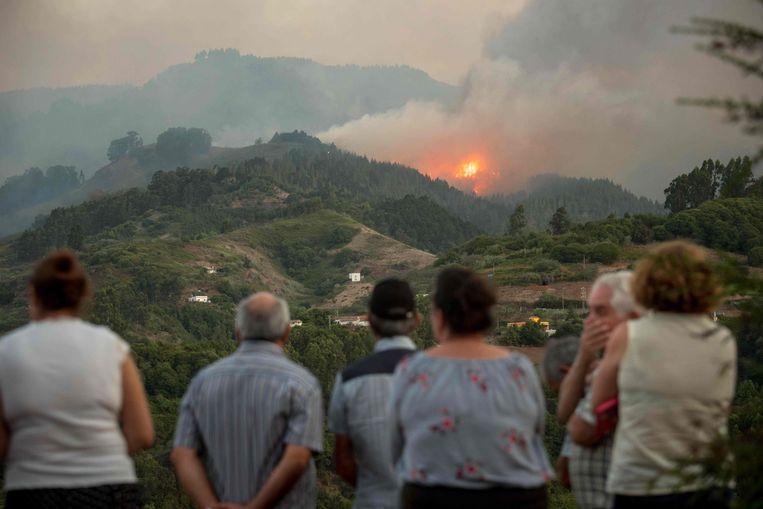 Inwoners van Montana Alta kijken toe hoe het vuur zich verspreidt.