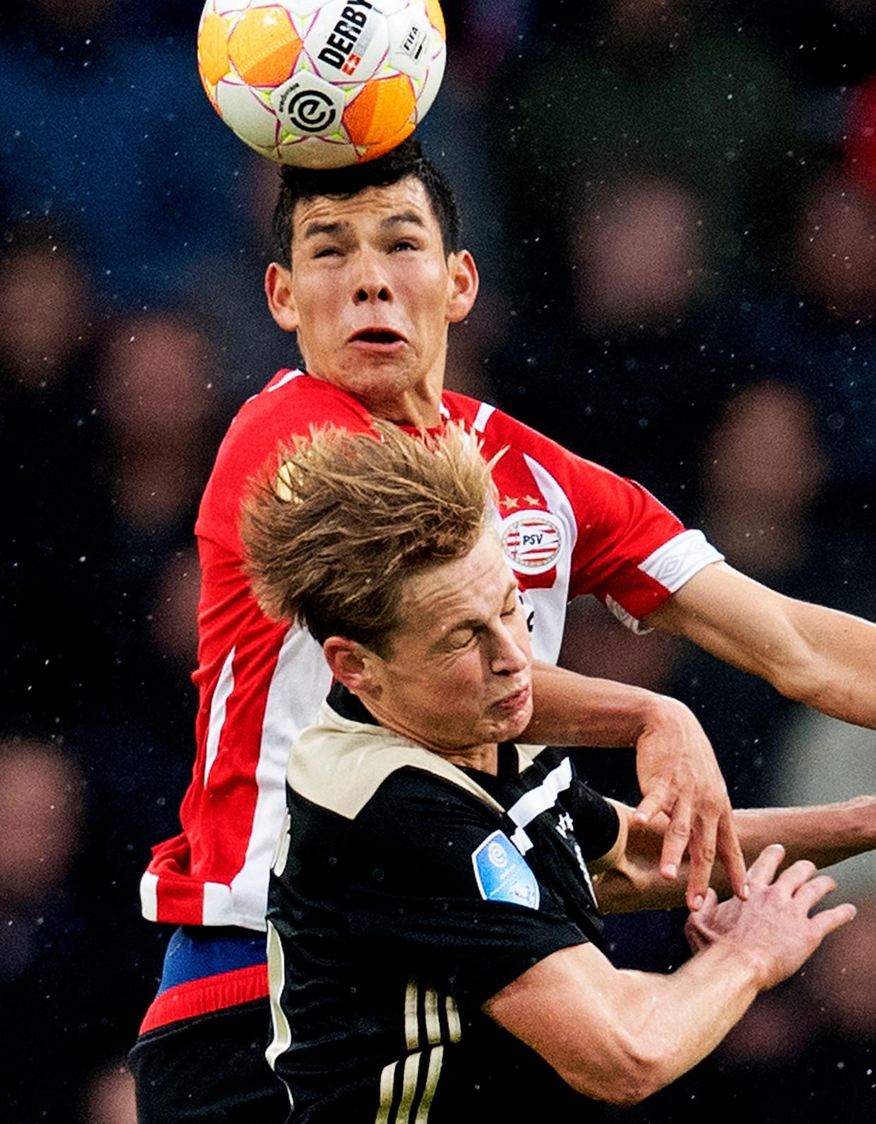 PSV-spits Lozano wint het kopduel met Ajacied De Jong tijdens PSV - Ajax in september. PSV won en staat in de eredivisie twee punten voor op Ajax.