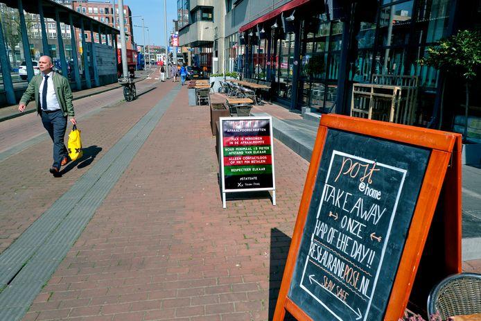 Een bord met 'Take Away' op de stoep bij restaurant Post in Dordrecht.