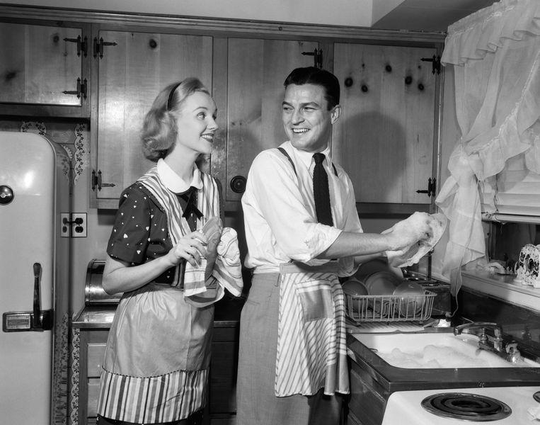 Een man doet de afwas in de jaren vijftig.  Beeld null