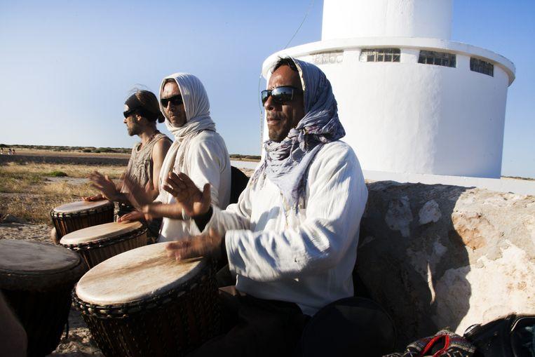 Een groep vrienden speelt percussie bij de vuurtoren van Cap de Barbaria. Beeld Eva Roefs