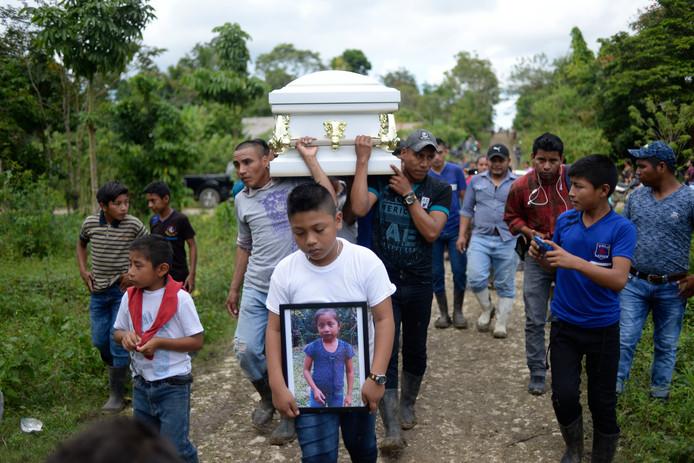 Een jongen toont een foto van het overleden meisje Jakelin Caal, terwijl familie en buren haar kist dragen naar de begraafplaats in het dorpje San Antonio Secortez in Guatemala.