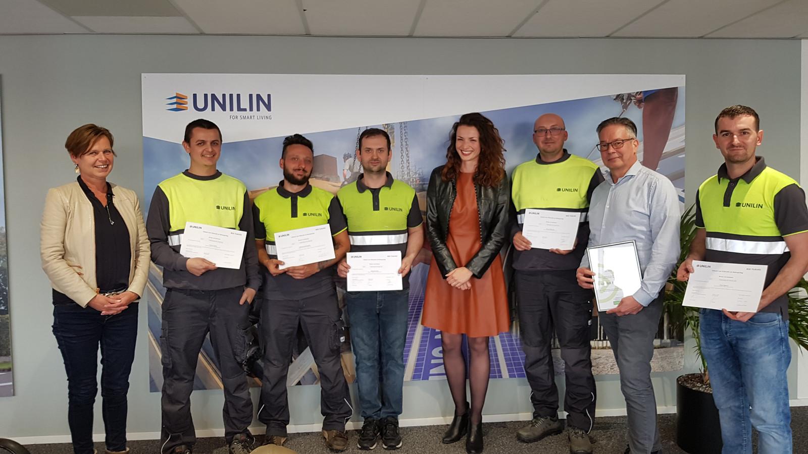 Arbeidsmigranten, met de Oisterwijkse wethouder Stefanie Vatta in hun midden, ontvingen bij Unilin een taalcertificaat