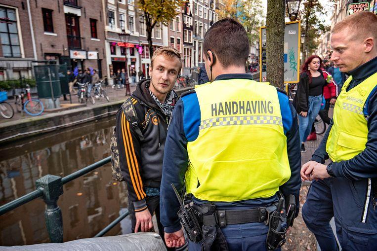 Boa's doen hun ronde in het centrum van Amsterdam en houden een man aan vanwege openbaar dronkenschap. Beeld Guus Dubbelman / de Volkskrant