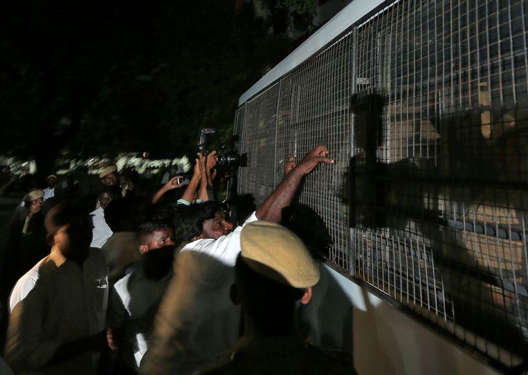 Een man probeert het traliewerk van de ramen van een politiewagen te trekken waarin de verdachten worden vervoerd.