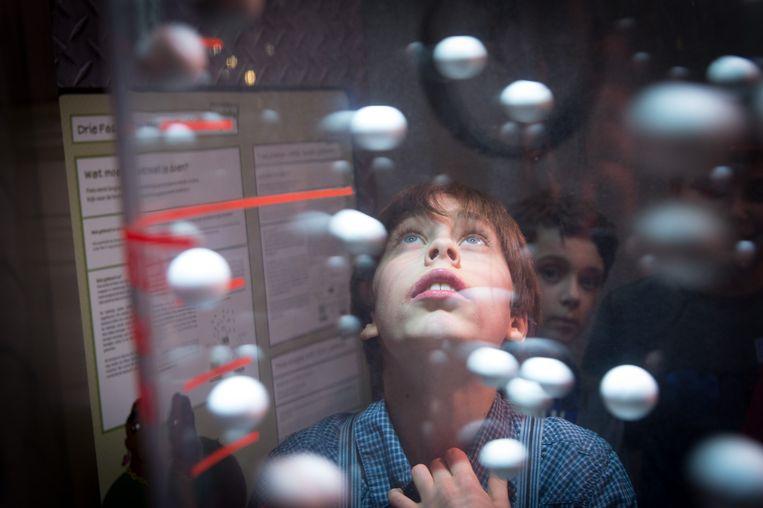 Een leerling kijkt vol bewondering naar een van de opstellingen.