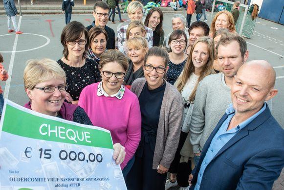 Isabelle Vergucht en Sylvia Decocker van de oudervereniging overhandigen de cheque aan directeur Jan Goethals.