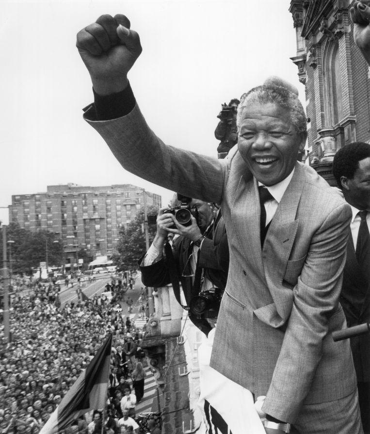Nelson Mandela bij een bezoek aan Nederland in 1990, vanaf het balkon van de Stadsschouwburg in Amsterdam.    Beeld Hollandse Hoogte / Willem Middelkoop