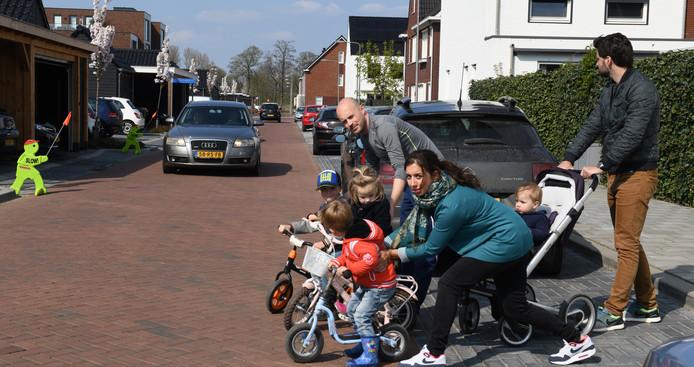 De ouders Linda en Gerrit van Wijk en Mattin Harmanny houden hun kinderen vast totdat een auto is gepasseerd op het Van Barnevelderf in Veenendaal.