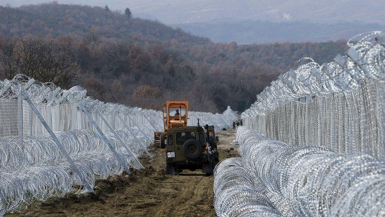Macedonië is bezig een hek te bouwen langs zijn grens met Griekenland. Het bestaat uit twee rijen hekwerk, versterkt met scheermesdraad. Beeld AP
