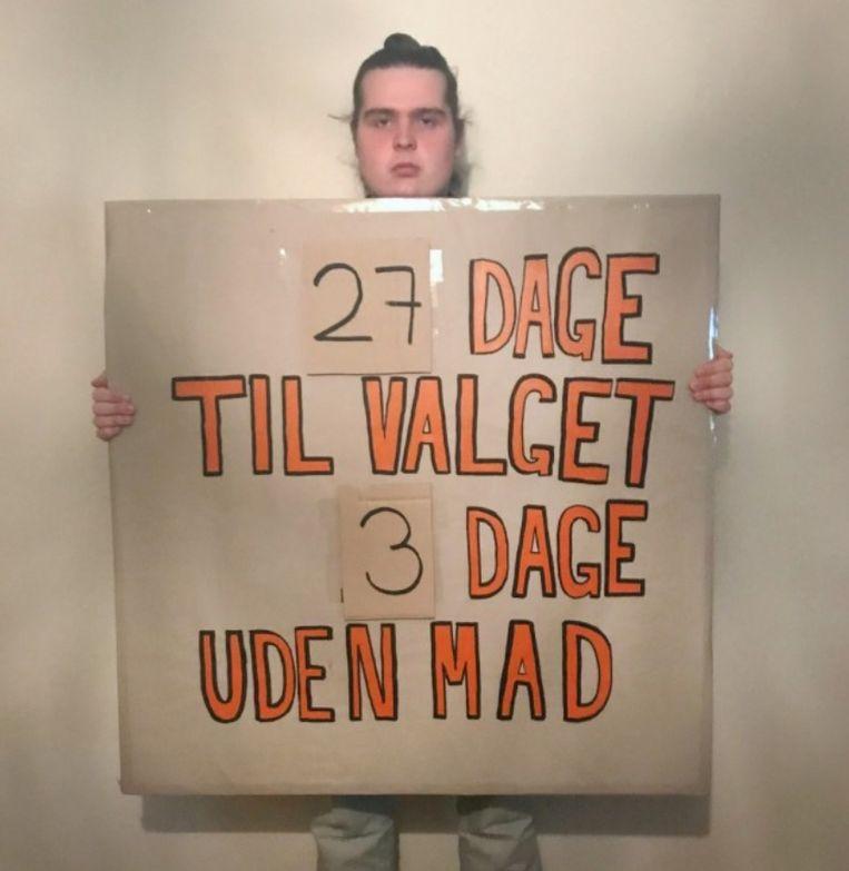 """""""27 dagen voor de verkiezingen, drie dagen zonder voedsel"""", staat te lezen op het kartonnen bord dat hongerstaker Mikkel Brix vasthoudt."""