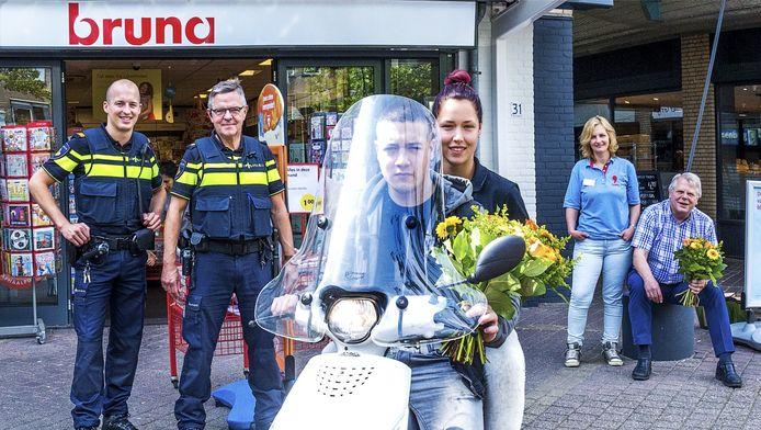 Kylian Haack en Aimee van den Bovenkamp op de scooter waarmee zij de winkeldief achtervolgden. Zij worden geflankeerd door Hans en Angelique Schenk (r.) en de wijkagenten Wietse Hamming en Rick-Jan Godschalk.