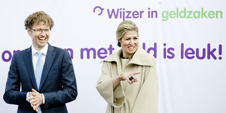 Sander Dekker met Maxima tijdens de opening van de Week van het geld. Achter hen de tekst 'Omgaan met geld is leuk!' Beeld null