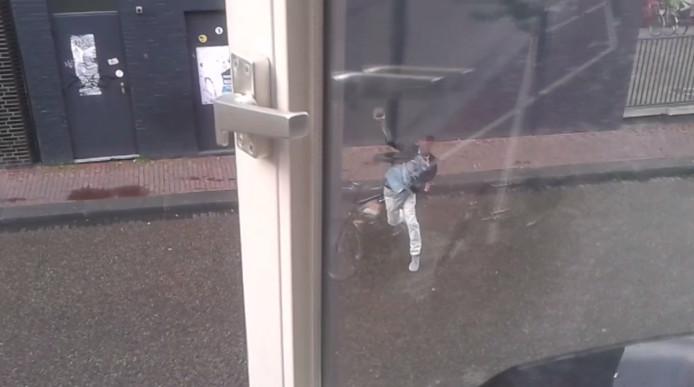 Een gefilmde dealer gooit woedend een steen door de ruit van de filmer.