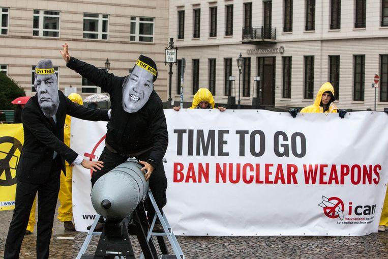 Een ICAN-actie in Berlijn, met actievoerders uitgedost als de Amerikaanse president Donald Trump en de Koreaanse leider Kim Jong Un.  Beeld Getty Images