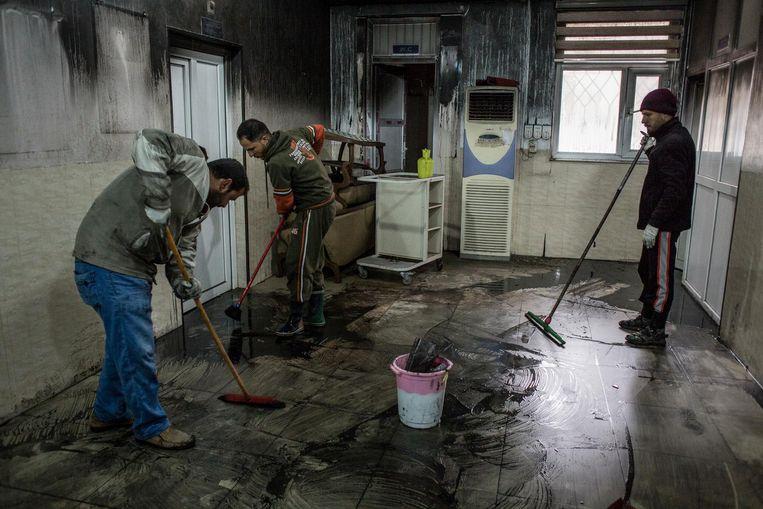 Artsen poetsen de zwartgeblakerde intensive care van het Ibn al Atheer-kinderziekenhuis. Beeld Hawre Khalid