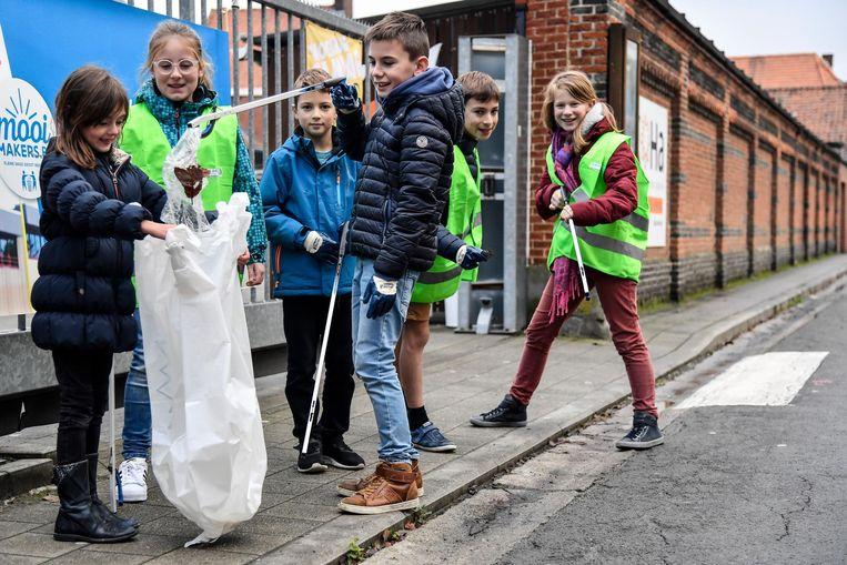 De kinderen maken de straten rond de school proper.