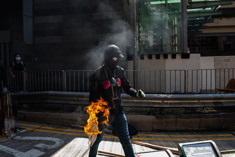 Een Honkongse betoger maakt zich klaar om een molotovcocktail te gooien.