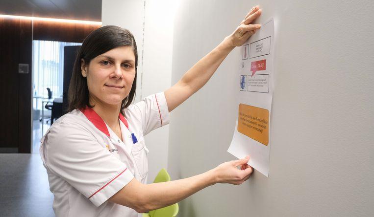 Ziekenhuishygiëniste Heidi Bruyneel hangt een affiche uit in de dienst pneumologie in het ziekenhuis AZ Groeninge.