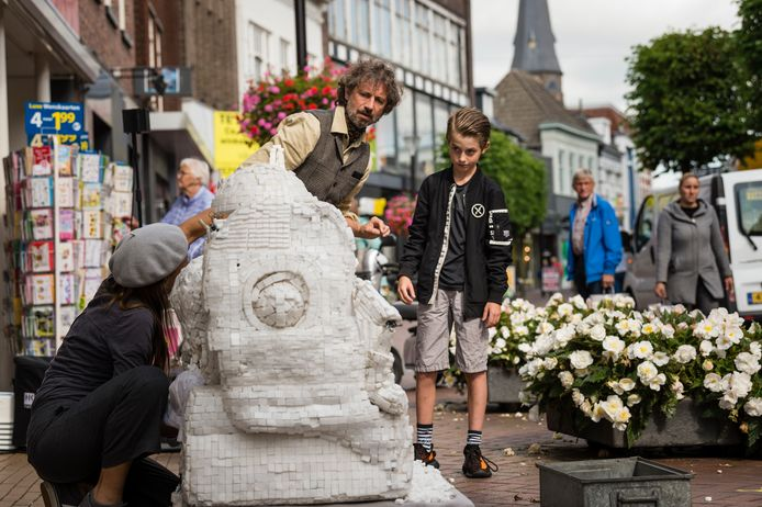 Straattheater in Almelo: Jason Sonneberg (midden) helpt de Trunk Puppeteers met de bouw van een kathedraal van suikerklontjes in de Grotestraat.