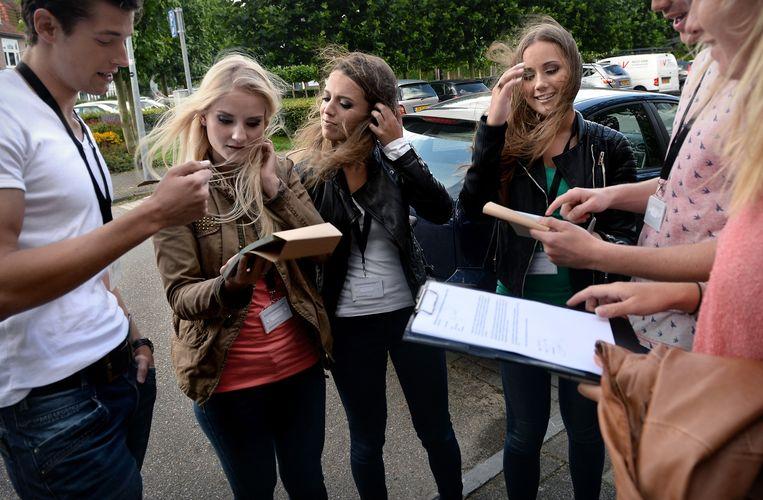 Jongeren in Haarlem nemen de looproutes door van de goede doelen waarvoor ze langs de deur gaan. Beeld Marcel van den Bergh / de Volkskrant