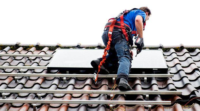 Een installateur plaatst zonnepanelen op het dak van een woning.